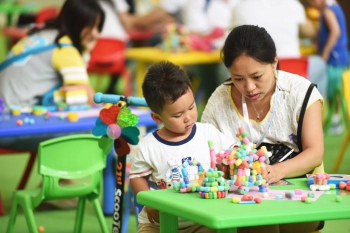 Một bà mẹ Trung Quốc và con trai tại khu vực vui chơi dành cho trẻ em tại một salon ô-tô của Bắc Kinh, ngày 26 tháng 6, 2015. (Ảnh: Wei yao/Imaginechina/via AFP)